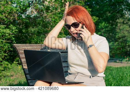 Young Woman With Red Hair With A Laptop Talking On The Phone On A Park Bench. The Woman Is Arguing A