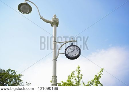 Clock On A Vintage Retro Post In The Park. Dial Against A Blue Sky On A Sunny Day. Street Clock