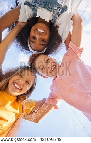 From Below Of Group Of Multiethnic Teen Friends Hugging And Looking At Camera On Background Of Sky