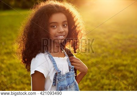 Cheerful African American Girl With Rucksack Standing In Back Lit In Park And Looking At Camera