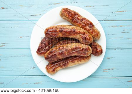 Grilled Sausages On White Plate On Blue Background. Top View