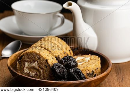 Side View Of Homemade Prune Sponge Cake Roll And Dried Pitted Prune Fruits In Wooden Bowl With White