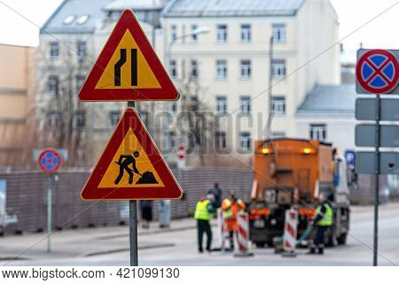 Warning Signs About Street Repairs On A Blurred Background With Repair Workers, Close-up