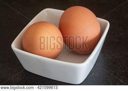 Two Fresh Eggs In A White Ramekin