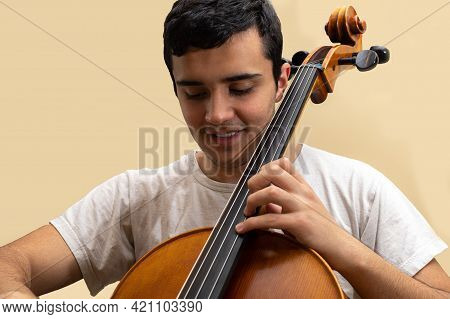 Young Teenage Girl Smiling And Playing Fretted String Musical Instrument Cello Placing Notes With Le