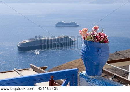 Close-up Of A Blue Vase With Flowers On A Terrace In Santorini With An Aerial View Of The Sea And Ca