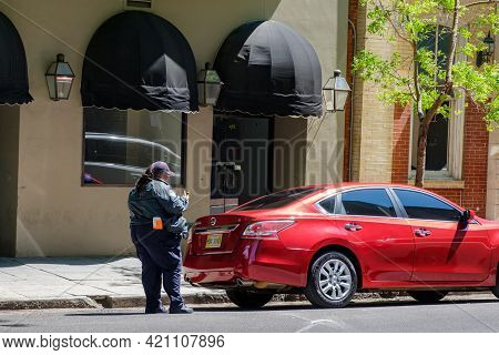New Orleans, La - April 21: Parking Control Officer Writes A Ticket For An Illegally Parked Car On D
