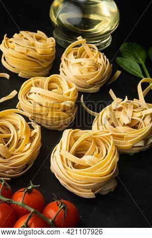 Raw Pasta Tagliatelle With Fresh Tomatoes And Herbs Set, On Black Stone Background