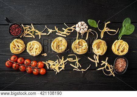 Ingredient Of Traditional Mediterranean Cuisine Uncooked Pasta Tagliatelle Set, On Black Wooden Tabl