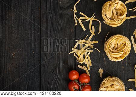 Rolled Tagliatelle Shape Of Italian Pasta With Ingredients Set, On Black Wooden Table Background, To