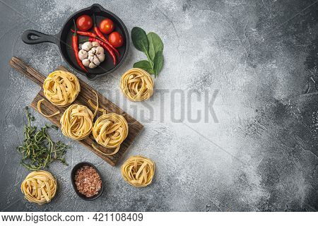 Rolled Tagliatelle Shape Of Italian Pasta With Ingredients Set, On Gray Stone Background, Top View F