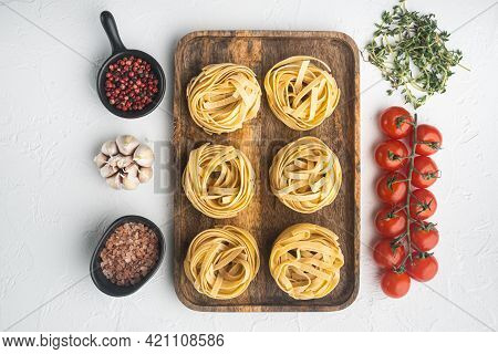 Raw Pasta Tagliatelle With Fresh Tomatoes And Herbs Set, On White Stone  Background, Top View Flat L