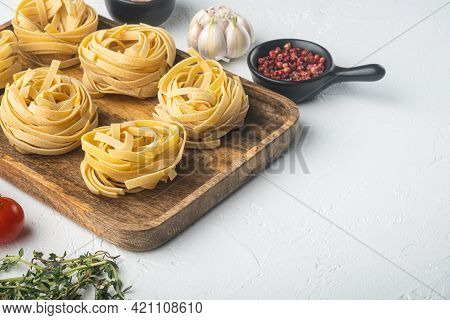 Rolled Tagliatelle Shape Of Italian Pasta With Ingredients Set, On White Stone  Background, With Cop