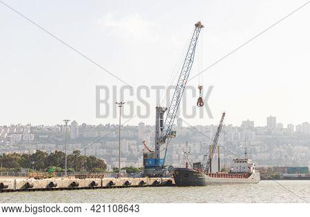 Haifa, Israel, May 08, 2021 : A Small Cargo Crane Unloads A Cargo Ship At The Dock At The Haifa Carg