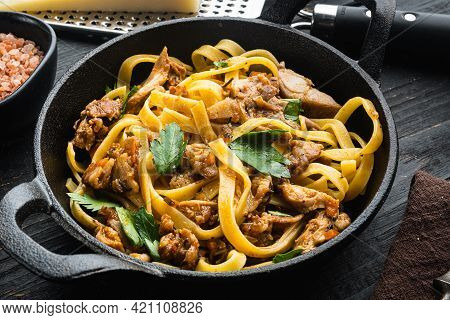 Rabbit Stew Tagliatelle Set, In Frying Cast Iron Pan Or Pot, On Black Wooden Table