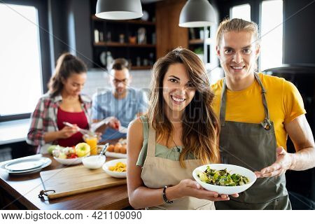 Group Of Happy Friends Having Fun In Kitchen, Cooking Food Together
