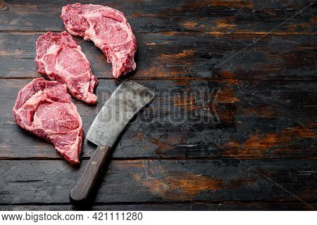 Rib Eye Steak Of Beef Marbled Meat Or Scotch Fillet Set, And Old Butcher Cleaver Knife, On Old Dark
