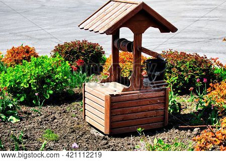 Decorative Rustic Wood Well And Flower Bed. The Idea For Landscaping And Landscaping Of The Territor