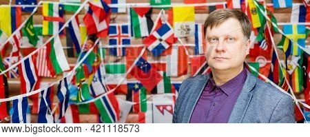 Strict Man Stands Against The Background Of Flags In The Room.