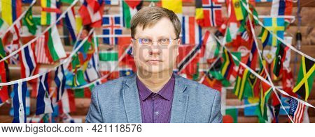 A Strict Man In Glasses Stands Against The Background Of Flags In The Room.