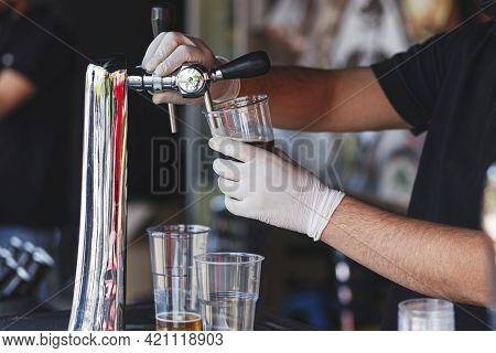 Barman Pouring Fresh Beer In Plastic Cup At Street Food Festival, Close Up. Man Hands In Gloves Pour