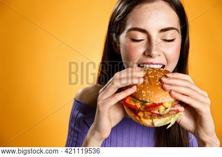 Girl Bites Cheeseburger With Satisfaction. Woman Eating Delicious Hambuger With Pleasure And Smile,