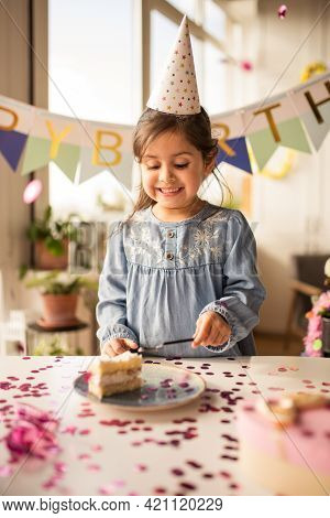 Girl Eating Her Birthday Cake With Happy Smile At The Birthday Party At Home