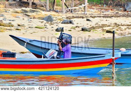 Labuan,malaysia-april 25,2021:fishermen Carry Suzuki Outboard Motor To The Boat Ready To Fishing At