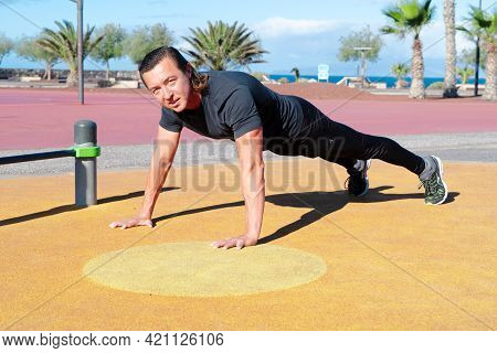 Sport Workout Of Caucasian Men, Flexing On Outdoor Sports Ground