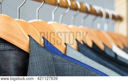 Mens Shirts, Suit Hanging On Rack. Hangers With Jackets On Them In Boutique. Suits For Men Hanging O