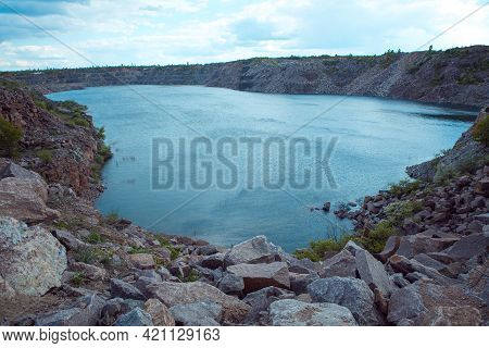 Beautiful Coast Of The Kamenka River In Spring. Colorful Landscape With Lake, Stones And Grass, Blue