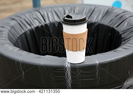 May 14, 2021 Santa Monica California, USA: Generic paper coffee cup on the side of a trash can with a plastic liner. Paper Coffee Cups are used world wide to drink coffee and soda. Editorial Use.