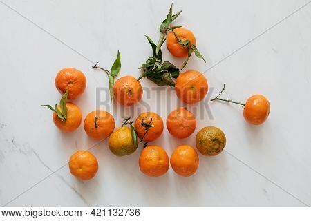 Bright clementines on a marble countertop