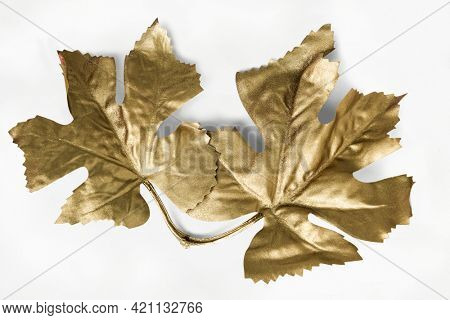 Maple leaves painted in gold on an off white background
