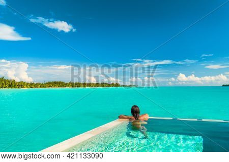 Luxury swimming pool spa resort travel honeymoon destination woman relaxing in infinity pool at hotel nature background summer holiday.