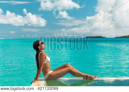 Luxury hotel swimming pool spa Asian bikini woman sunbathing on pool edge of Tahiti Bora Bora honeymoon destination resort. Blue turquoise crystalline waters background.