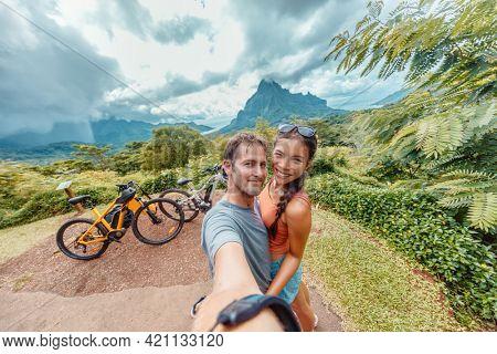 E-bike biking couple taking seflie on bikepacking travel vacation. Interracial tourists Asian woman, Caucasian man happy having fun on Moorea island ride, Tahiti, French Polynesia holiday adventure.