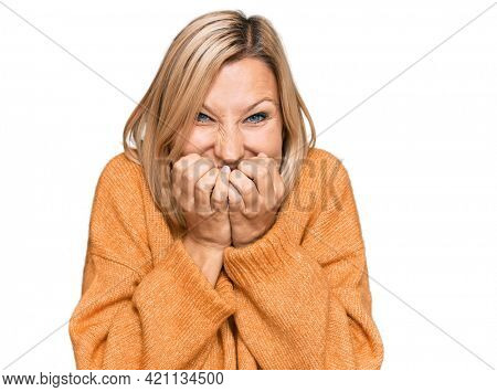 Middle age caucasian woman wearing casual winter sweater laughing and embarrassed giggle covering mouth with hands, gossip and scandal concept