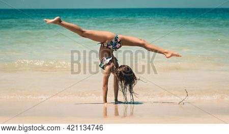 Little Sportive Girl with Pleasure Practicing Acrobatic Tricks on the Beach. Doing Sport Outdoors. Healthy Lifestyle. Happy Summer Vacation.