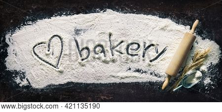 Baking background with a heart shape and text Bakery handwritten in flour and rolling pin on dark table