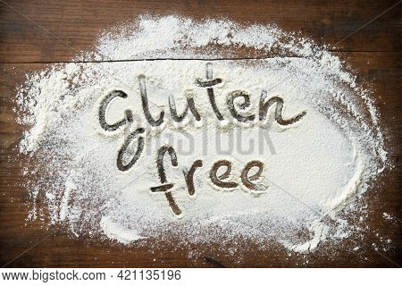 Baking background with flour on wooden table. Text Gluten free is handwritten in flour. Healthy eating concept