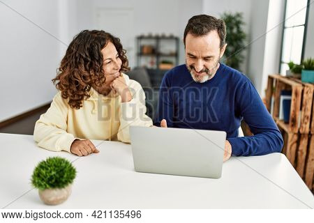 Middle age hispanic couple smiling happy using laptop at home.