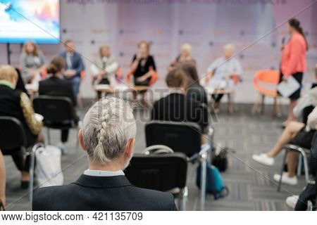 Audience listens to female speaker at conference hall, rear view