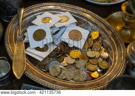 From above of assorted golden and silver coins in tray placed on counter at antique bazaar