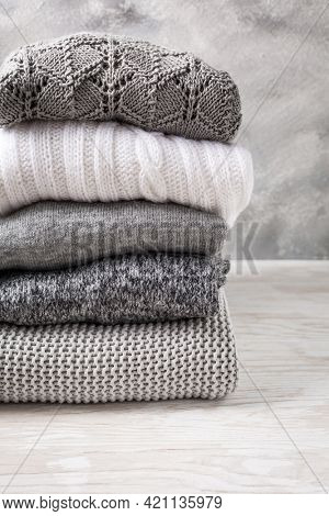 Stack of cozy knitted sweaters and pullovers on wooden background. Autumn and winter concept