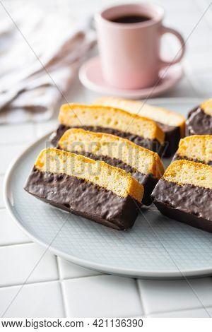Sliced sponge dessert. Sweet sponge cake with chocolate on white kitchen table.