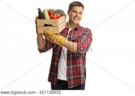 Young male farmers carrying crate with vegetables on his shoulder and smiling isolated on white background