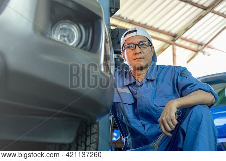 Technician Or Garage Worker Sit Beside Of Car And Look At Camera During Work In Workplace Area. Gara