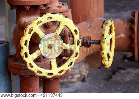 Two Brown Retro Design Industrial Valves With Yellow Handwheels Over Concrete Industrial Background