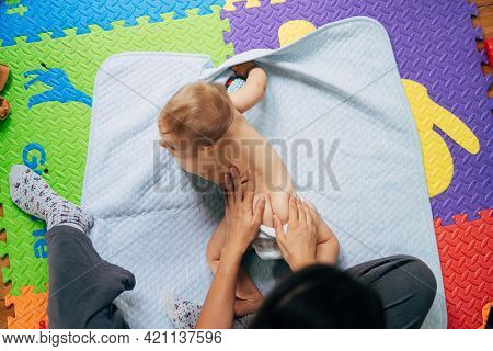 Baby In Diapers Lies On His Tummy On A Blue Blanket Over A Colored Rug On The Floor. Mom Put Her Han